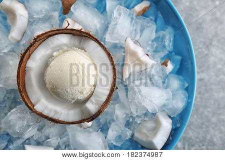 Half of coconut with fresh ice cream ball cooling on icy cubes in blue bowl