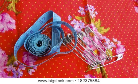 Blue tape measure and pins on red cloth