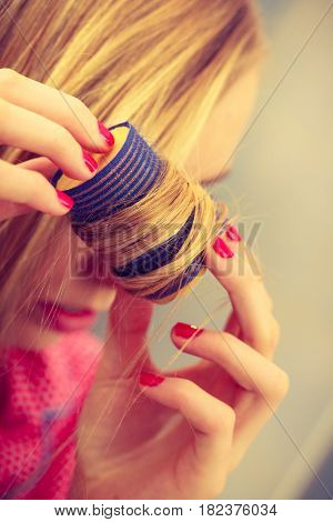 Woman curling her blond hair using rollers