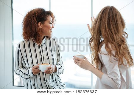 Two women sitting near the window in cafe and looking away