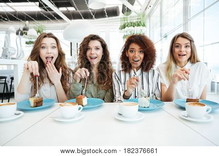 Four friends sitting by the table and eating cakes in cafe while looking at the camera