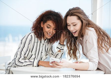 Two women sitting by the table in cafe and using smartphone