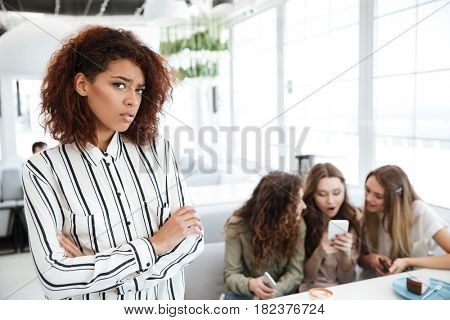 Upset african woman standing near her three friends which sitting by the table in cafe and using smartphone
