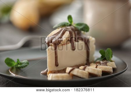 Tasty cheesecake slice with chocolate and bananas on plate