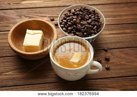 Composition with tasty butter coffee on wooden table