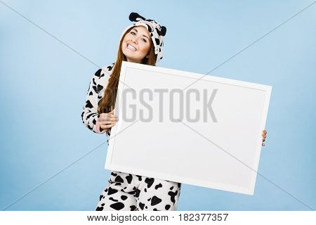 Smiling teenage girl in funny nightclothes pajamas cartoon style with blank empty banner board. Advertisement copyspace.