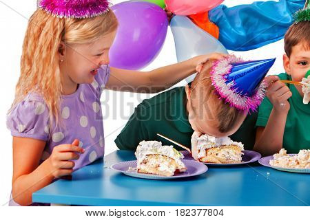 Birthday children celebrate party and eating cake on plate together . Portrait of three fun kids happy girl and boy in party hat and messy face have cake fight .
