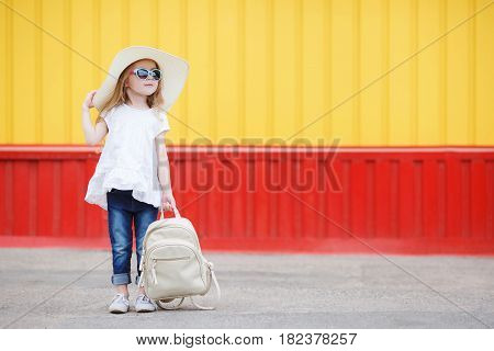 Beautiful little girl 6-8 years old,in a large straw hat from the sun,dressed in a short white dress without sleeves and blue jeans,with long blonde wavy hair and wears dark sun glasses in blue frame,posing standing near the school with a white backpack