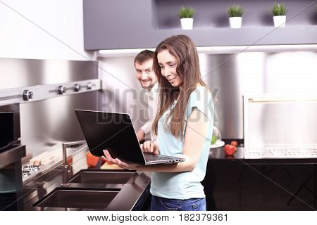 Couple in front laptop computer in the kitchen at home