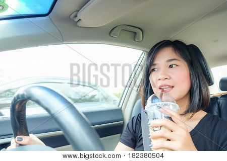 Asian Woman Driving A Car With Coffee Drink