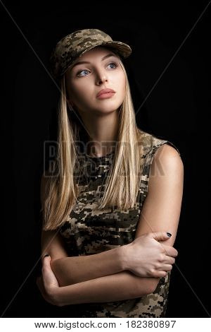 portrait of a beautiful blond woman soldiers in military attire on black background