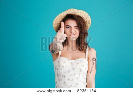 Portrait of a serious young girl in straw hat making gun gesture with fingers and pointing at camera isolated over blue background