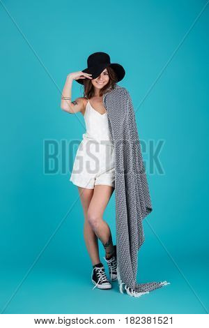 Full length portrait of a young smiling summer girl wearing hat and blanket over her shoulder isolated over blue background