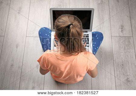 Incorrect posture concept. Cute schoolgirl with laptop sitting on floor