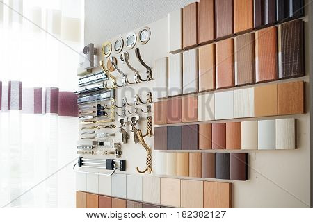 Stand with a sample of laminated chipboard and furniture fittings in the furniture salon. Furniture fittings multicolored chipboard panels close-up background laminated chipboards