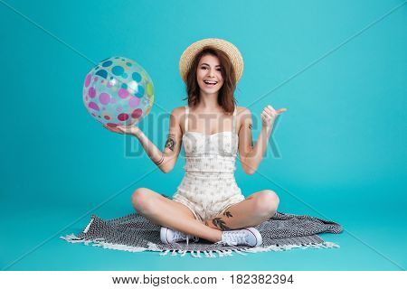 Portrait of a happy cheerful summer girl in straw hat sitting on a blanket with beachball and showing thumbs up gesture isolated over blue background
