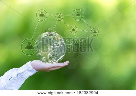 Terrestrial globe with networking system in male palm on abstract green background. Elements of this image furnished by NASA