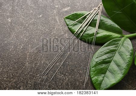 Needles for acupuncture on dark textured background