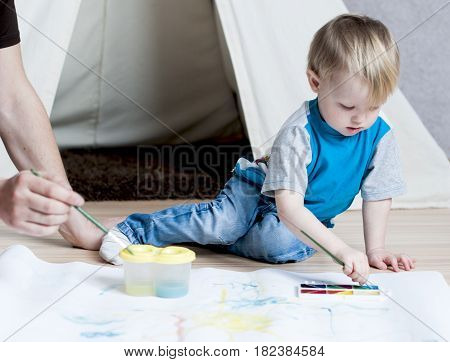 Cute kid with father draws a brush on white paper with watercolor paints behind the lodge