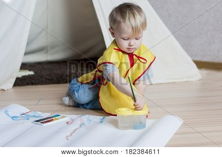 The kid in a yellow waistcoat draws a brush on a white paper with watercolors and behind the wigwam.