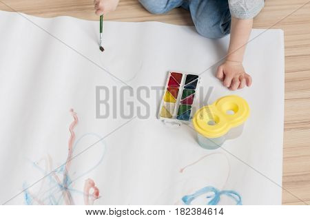 The kid learns to hold the brush and draw with watercolors indoor