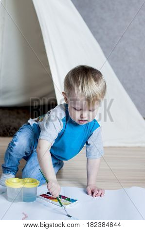 Concentrated kid draws a brush with watercolor paint behing the wigwam indoor