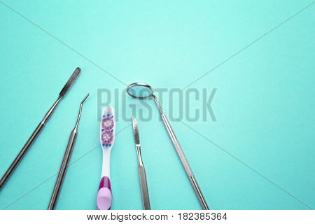 Toothbrush and dental instruments on color background