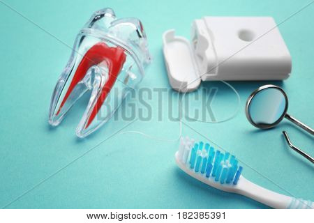 Toothbrush, plastic tooth mockup, dental instruments and floss on color background