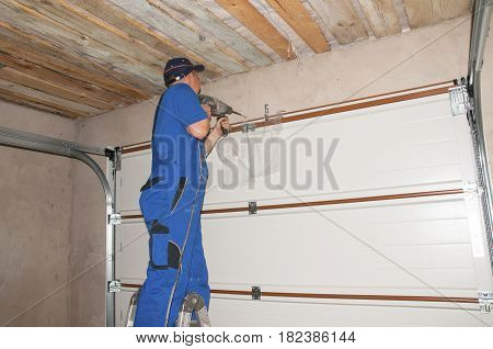 KIEV - UKRAINE APRIL - 24, 2017:  Contractor Installing Garage Door Opener. Garage door springs garage door replacement garage door repair.