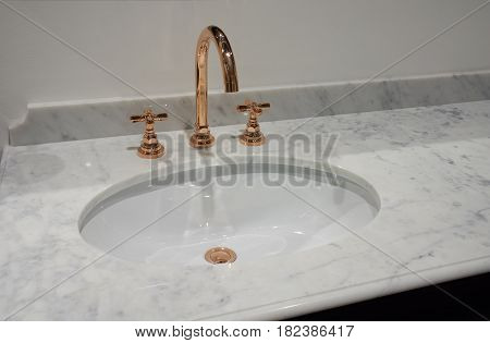 White inset ceramic washbasin in marble table and copper metal mixer