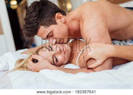 Happy couple in bedroom enjoying sensual foreplay