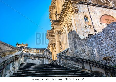 Scenic view at old famous public staircase in town Dubrovnik with historic church in background, Croatia Europe.