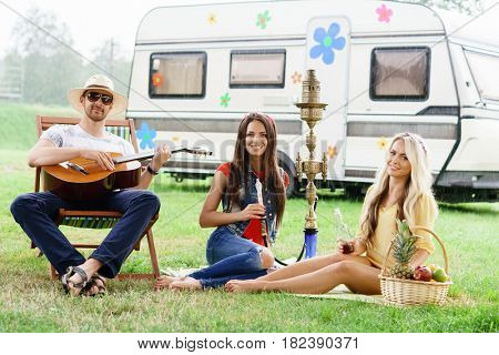 Happy, smiling friends having a picnic outdoors. Summer, trip, holiday spare time concept.