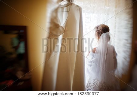 Bride On Silk Robe Looking On Window With Wedding Dress At Room On Morning Day.