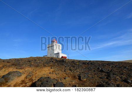 Vik Iceland's Dyrholaey Lighthouse against a blue sky.