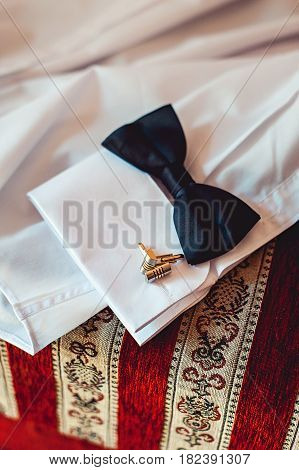 bowtie belt and cufflinks on a white shirt. Grooms morning