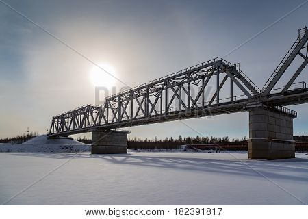 Railway bridge in winter with the sun in the sky covered with haze