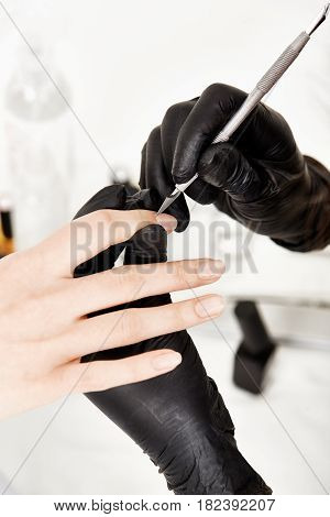 Nail artist correcting manicure with steel cuticle remover after applying base coat on nails.