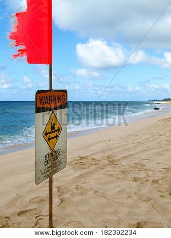 Strong current warning sign on shore at the ocean
