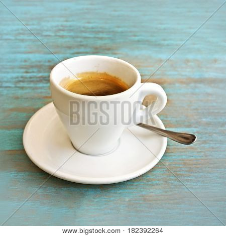 A square photo of a white cup of coffee on a teal blue table in a cafe