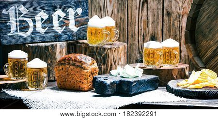 Mugs of beer, bread loaf and potato chips on raw wood pub counter with natural stumps and oak barrel. Wood signboard with text 'Beer'