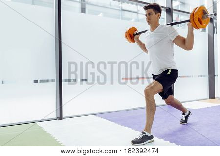 Handsome man exercising and lifting weights in fitness club