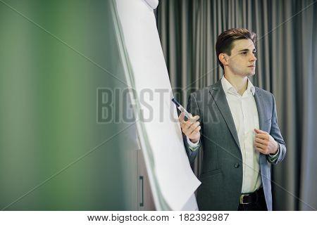Portrait Of A Confident Businessman Making Presentation On Flipchart In Modern Office