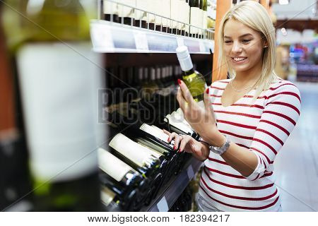 Woman deciding what wine to buy and shopping in supermarket