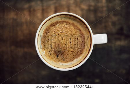 Close-up of coffee cup with froth on wooden table background. Concept of beverage and breakfast.