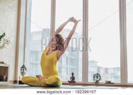 Fit young woman is sitting in lotus position and stretching arms up with enjoyment