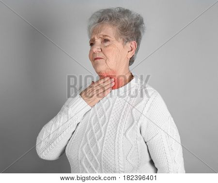 Allergies and sore throat concept. Sick senior woman on gray background