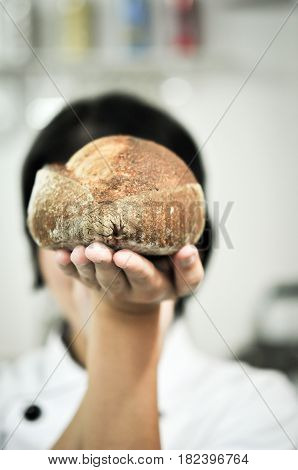 Mixed rye-wheat whole grain homemade sourdough bread on chef hand