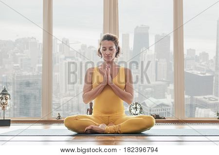 Stay calm and healthy. Portrait of sensual young woman is sitting in lotus position and meditating. Her eyes are closed with pleasure. City view from window on background