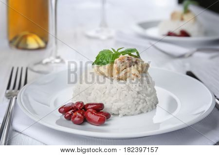 Delicious dish with chicken, rice and beans on white plate